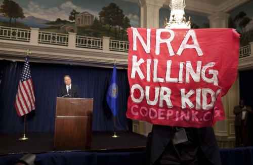 A protester holds up a sign as National Rifle Association executive vice president Wayne LaPierre, left, speaks during a news conference in response to the Connecticut school shooting on Friday, Dec. 21, 2012 in Washington.  (AP Photo/ Evan Vucci)