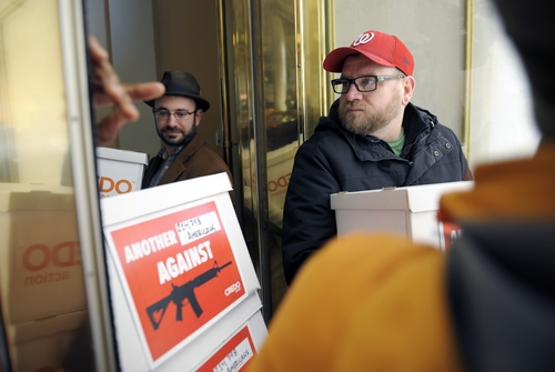 Members of Credo Mobil anti-National Rifle Association protestors are denied entrance to the front door of the Willard InterContinental Hotel after they attempted to deliver a petition to the National Rifle Association which is having a news conference in Washington, Friday, Dec. 21, 2012. The petition calls on the NRA to get out of the way of gun control legislation. (AP Photo/Cliff Owen)