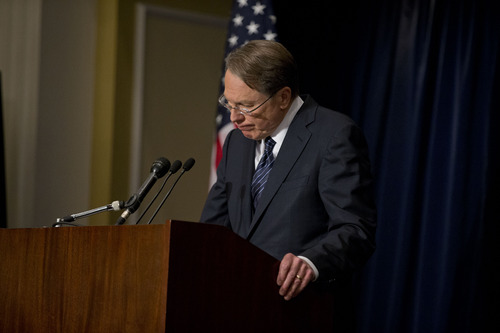 "The National Rifle Association executive vice president Wayne LaPierre ,pauses as he makes a statement during a news conference in response to the Connecticut school shooting on Friday, Dec. 21, 2012 in Washington.  The nation's largest gun-rights lobby is calling for armed police officers to be posted in every American school to stop the next killer ""waiting in the wings.""   (AP Photo/ Evan Vucci)"