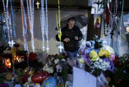 Ben Toby of Sandy Hook visits a memorial to the Newtown shooting victims during a heavy rain in the Sandy Hook village of Newtown, Conn., Friday, Dec. 21, 2012.  The shooter, Adam Lanza, walked into Sandy Hook Elementary School in Newtown, Dec. 14, and opened fire, killing 26 people, including 20 children, before killing himself. (AP Photo/Seth Wenig)