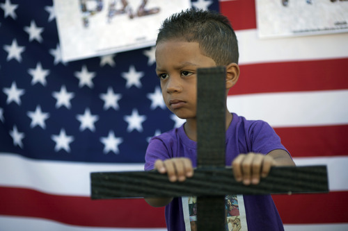 A boy holds a cross outside the Tasso da Silveira elementary school where a gunman killed 12 children in April 2011, as part of a protest against violence in schools in the Realengo neighborhood of Rio de Janeiro, Brazil, Friday, Dec. 21, 2012. Family members and neighbors of the victims held the protest in light of the recent school shooting in Newtown, Conn.  A U.S. flag hangs behind him. (AP Photo/Felipe Dana)