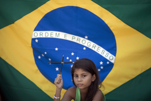 Larissa Vitoria, 7, who lives across the street from the Tasso da Silveira school where 12 children were killed by a gunman in April 2011, holds a cross made of pencils during a demonstration to protest violence in schools in the Realengo neighborhood of Rio de Janeiro, Brazil, Friday, Dec. 21, 2012. Family members and neighbors of the victims held the protest in light of the recent school shooting in Newtown, Conn.  A Brazilian flag hangs behind her. (AP Photo/Felipe Dana)
