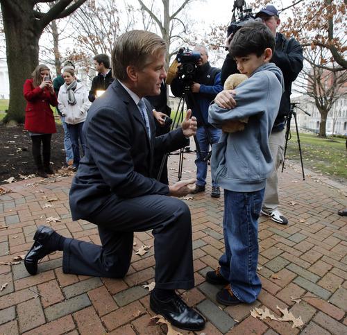 """Virginia Gov. Bob McDonnell, left, kneels down to talk with Gabriel Smith, 11, who holds onto """"Teddy"""" after a ceremony of remembrance for the victims of the Connecticut shooting at the Bell Tower in Capitol Square in Richmond, Va., Friday, Dec. 21, 2012. At the ceremony, the bell was chimed 26 times during a moment of silence.  (AP Photo/Richmond Times-Dispatch, Bob Brown)"""