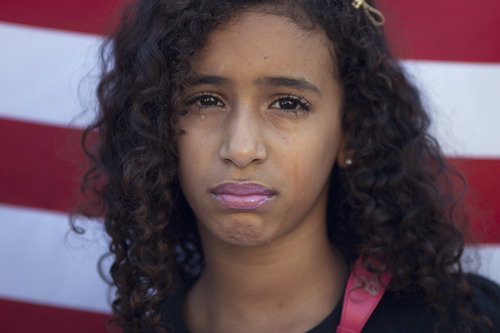 Maria Julia, 8, whose cousin Luiza died along with 11 other students in an April 7, 2011 school shooting, looks toward the camera as tears roll down her cheeks during a demonstration against violence in schools outside her cousin's school in the Realengo neighborhood of Rio de Janeiro, Brazil, Friday, Dec. 21, 2012. Family members of the victims held the protest in light of the recent school shooting in Newtown, Conn.  A U.S. flag hangs behind her. (AP Photo/Felipe Dana)