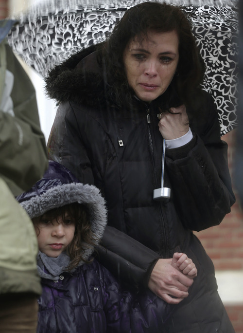 Sarah Baroody holds her daughter Sophia's hand and cries while observing a moment of silence as bells rang 26 times in Newtown, Conn., Friday, Dec. 21, 2012. The chiming of bells reverberated throughout Newtown, commemorating one week since the crackle of gunfire in a schoolhouse killed 20 children and six adults in a massacre that has shaken the community and the nation.  (AP Photo/Seth Wenig)