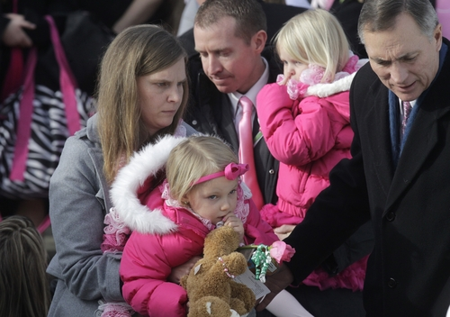 Alissa Parker, left, and her husband, Robbie Parker, center, carry their daughters following funeral services for their 6-year old daughter,  Connecticut elementary shooting victim, Emilie Parker, Saturday, Dec. 22, 2012, at The Church of Jesus Christ of Latter-day Saints, in Ogden, Utah. Emilie, whose family has Ogden roots, was one of 20 children and six adult victims killed in on the Dec. 14 mass shooting at Sandy Hook Elementary in Newtown, Conn.  (AP Photo/Rick Bowmer)