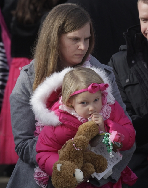 ADDS NAME OF DAUGHTER SAMANTHA - Alissa Parker carries her daughter, Samantha, 3,  following funeral services for her 6-year old daughter, Connecticut elementary shooting victim Emilie Parker, Saturday, Dec. 22, 2012, at the Church of Jesus Christ of Latter -Day, in Ogden, Utah. Emilie, whose family has Ogden roots, was one of 20 children and six adult victims killed in a Dec. 14 mass shooting at Sandy Hook Elementary in Newtown, Conn. (AP Photo/Rick Bowmer)