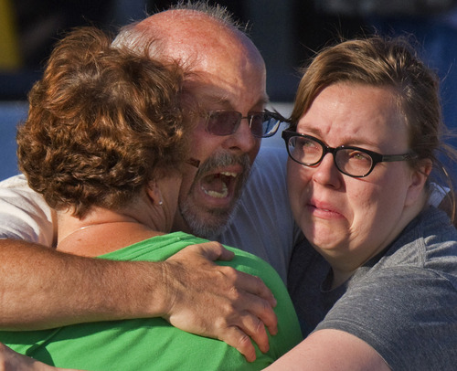 "Tom Sullivan, center, embraces family members outside Gateway High School where he has been searching for his son Alex Sullivan who celebrated his 27th birthday by going to see ""The Dark Knight Rises,"" movie where a gunman opened fire Friday, July 20, 2012, in Aurora, Colo. (AP Photo/Barry Gutierrez)"