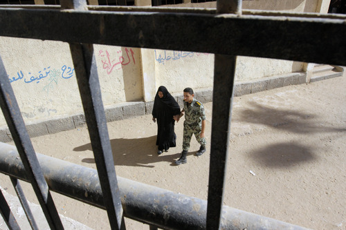 An Egyptian army officer helps an elderly woman as she enters to vote for the second round of a referendum on a disputed constitution drafted by Islamist supporters of President Mohammed Morsi in Giza, Egypt, Saturday, Dec. 22, 2012. (AP Photo/Amr Nabil)