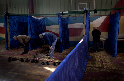 An Egyptian man votes while other voters perform the noon prayers at gymnasium hall used as a polling station during the second round of a referendum on a disputed constitution drafted by Islamist supporters of president Mohammed Morsi, in Giza, Egypt, Saturday, Dec. 22, 2012. (AP Photo/Nasser Nasser)
