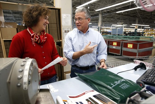 LL Bean CEO Chris McCormack, right, and company spokesman Carolyn Beem prepare packages for shipping at the company's order fulfillment center, Thursday, Dec. 20, 2012, in Freeport, Maine. At this time of the year the company's white-collar executives have abandoned their desks in favor of the shipping department at L.L. Bean, part of a final push to get things shipped in time for Christmas. (AP Photo/Robert F. Bukaty)