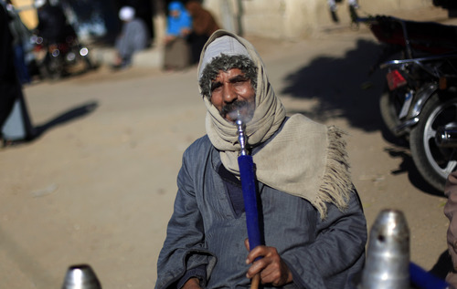 An Egyptian man smokes a water pipe outside a polling station as he waits to cast his vote during the second round of a referendum on a disputed constitution drafted by Islamist supporters of President Mohammed Morsi in Fayoum, about 100 kilometers (62 miles) south of Cairo, Egypt, Saturday, Dec. 22, 2012.(AP Photo/Khalil Hamra)