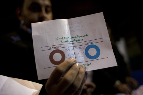 An Egyptian election worker shows his colleagues an invalid ballot while counting ballots at the end of the second round of a referendum on a disputed constitution drafted by Islamist supporters of president Mohammed Morsi at a polling station in Giza, Egypt, Saturday, Dec. 22, 2012. Egypt's Islamist-backed constitution headed toward likely approval in a final round of voting on Saturday, but the deep divisions it has opened up threaten to fuel continued turmoil. (AP Photo/Nasser Nasser)