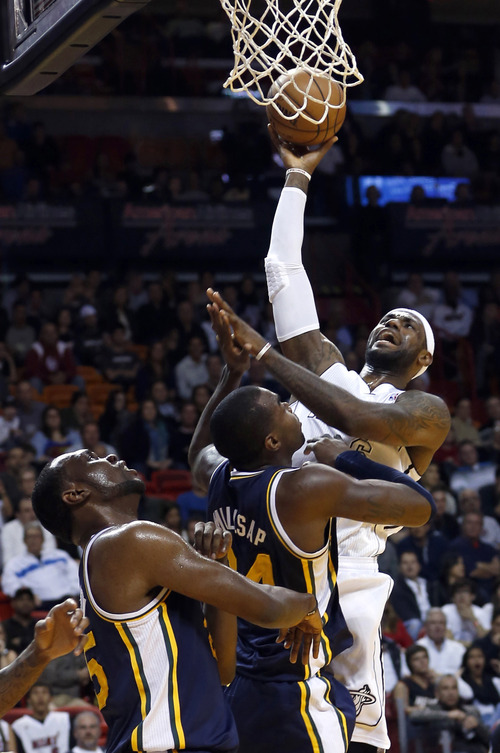 Miami Heat's LeBron James, right, shoots over Utah Jazz's Paul Millsap and Al Jefferson, left, during the first half of an NBA basketball game in Miami, Saturday, Dec. 22, 2012. (AP Photo/Alan Diaz)