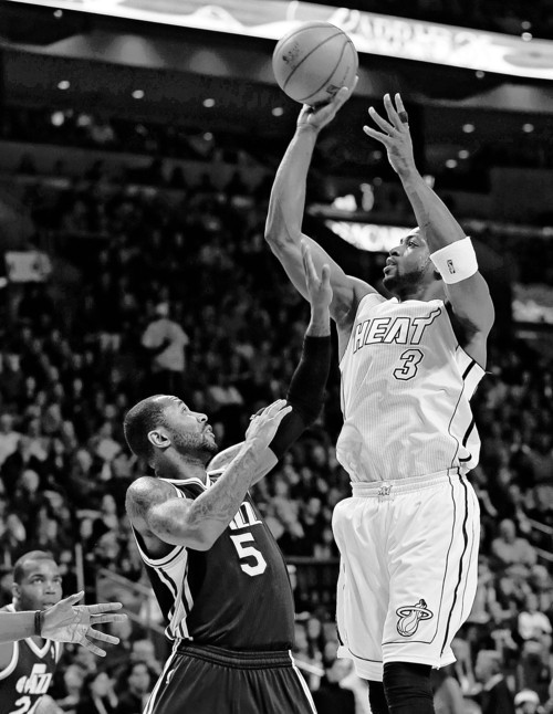 Miami Heat's Dwyane Wade (3) shoots over Utah Jazz's Mo Williams (5) during the first half of an NBA basketball game in Miami, Saturday, Dec. 22, 2012. (AP Photo/Alan Diaz)