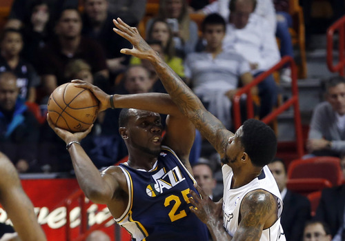 Miami Heat's Udonis Haslem pressures Utah Jazz's Al Jefferson (25) during the first half of an NBA basketball game in Miami, Saturday, Dec. 22, 2012. (AP Photo/Alan Diaz)