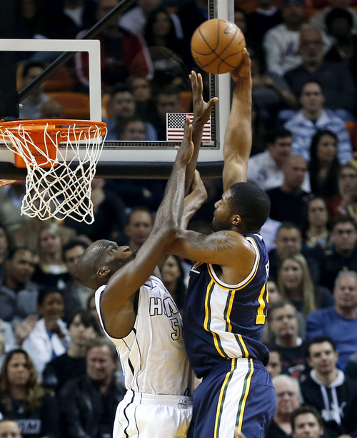 Utah Jazz's Derrick Favors (15) is fouled by Miami Heat's Joel Anthony (50) during the second half of an NBA basketball game in Miami, Saturday, Dec. 22, 2012. The Heat won 105-89. (AP Photo/Alan Diaz)