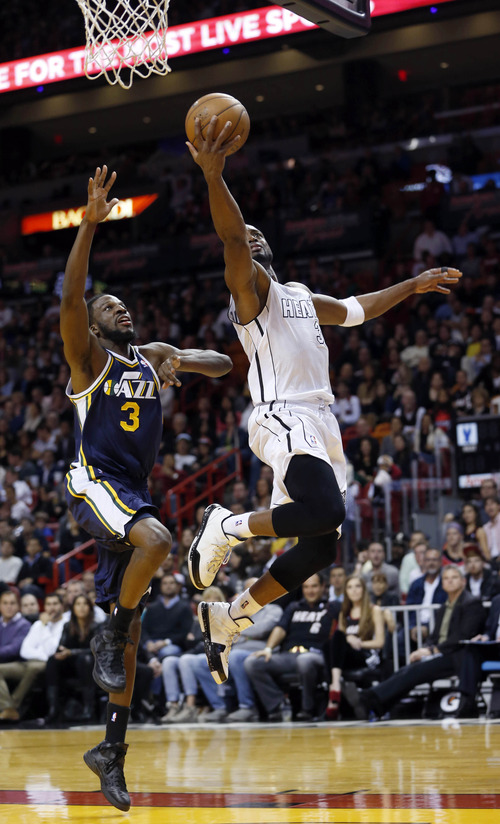 Miami Heat's Dwyane Wade, right, goes to the basket against Utah Jazz's DeMarre Carroll (3) during the second half of an NBA basketball game in Miami, Saturday, Dec. 22, 2012. The Heat won 105-89. (AP Photo/Alan Diaz)