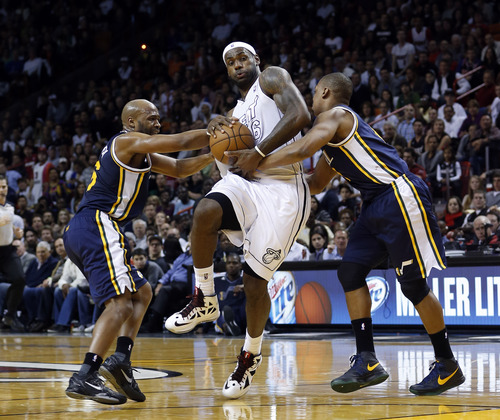 Miami Heat's LeBron James (6) is fouled by Utah Jazz's Randy Foye, right, and Jamaal Tinsley, left, defends during the second half of an NBA basketball game in Miami, Saturday, Dec. 22, 2012. The Heat won 105-89. (AP Photo/Alan Diaz)