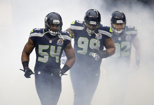 Seattle Seahawks middle linebacker Bobby Wagner (54), defensive tackle Alan Branch (99), and tight end Evan Moore (82) run onto the field before an NFL football game against the Arizona Cardinals in Seattle, Sunday, Dec. 9, 2012. (AP Photo/Stephen Brashear)