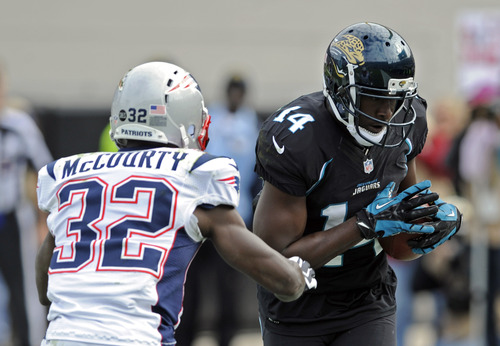 Jacksonville Jaguars wide receiver Justin Blackmon (14) catches a pass in the end zone in front of New England Patriots free safety Devin McCourty (32) for a touchdown during the first half of an NFL football game on Sunday, Dec.  23, 2012, in Jacksonville, Fla. (AP Photo/Stephen Morton)