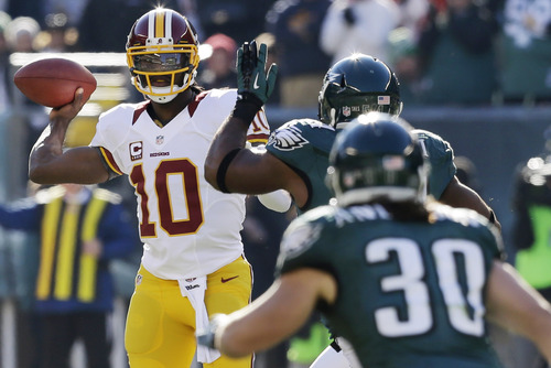 Washington Redskins quarterback Robert Griffin III, left, passes under pressure from Philadelphia Eagles' Brandon Graham, center, and Colt Anderson in the first half of an NFL football game, Sunday, Dec. 23, 2012, in Philadelphia. (AP Photo/Mel Evans)