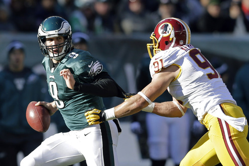 Philadelphia Eagles' Nick Foles, left, scrambles from Washington Redskins' Ryan Kerrigan in the first half of an NFL football game, Sunday, Dec. 23, 2012, in Philadelphia. (AP Photo/Mel Evans)