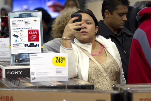 FILE - In this Thursday, Nov. 22, 2012, file photo a shopper uses her smart phone at the Pembroke Pines, Fla. Best Buy. Facebook isn't just for goofy pictures and silly chatter. Whether shoppers know it or not, their actions online help dictate what's in stores during this holiday season. (AP Photo/J Pat Carter, File)