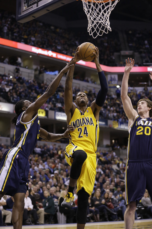 Indiana Pacers small forward Paul George, center is fouled by Utah Jazz shooting guard Gordon Hayward, right and small forward DeMarre Carroll in the first half of an NBA basketball game in Indianapolis, Wednesday, Dec. 19, 2012.  (AP Photo/Michael Conroy)