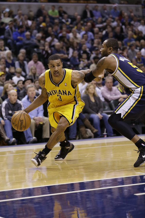 Indiana Pacers point guard George Hill, left, drives on Utah Jazz point guard Mo Williams in the first half of an NBA basketball game in Indianapolis, Wednesday, Dec. 19, 2012.  (AP Photo/Michael Conroy)