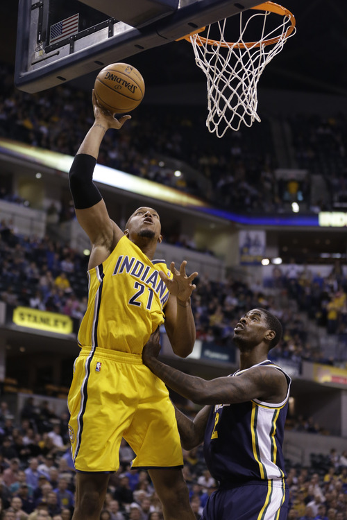 Indiana Pacers power forward David West, left, shoots over Utah Jazz power forward Marvin Williams in the first half of an NBA basketball game in Indianapolis, Wednesday, Dec. 19, 2012.  (AP Photo/Michael Conroy)