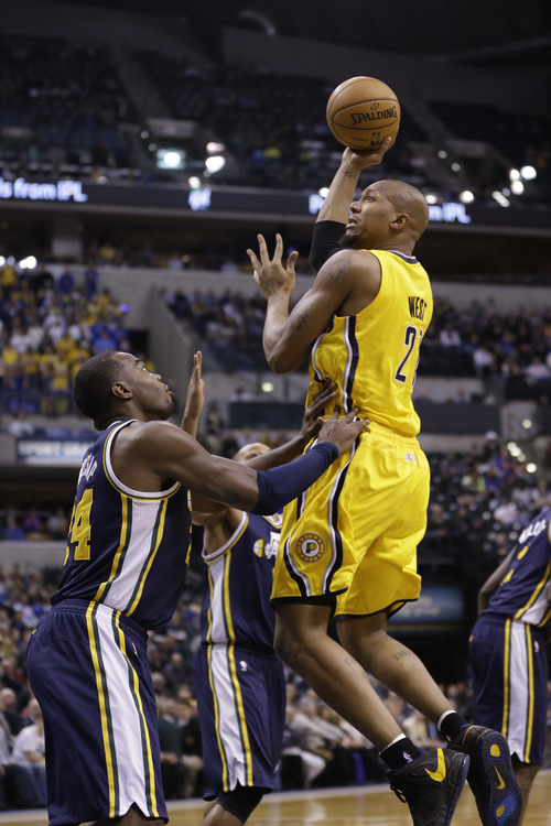 Indiana Pacers power forward David West, right, shoots over Utah Jazz power forward Paul Millsap in the first half of an NBA basketball game in Indianapolis, Wednesday, Dec. 19, 2012.  (AP Photo/Michael Conroy)