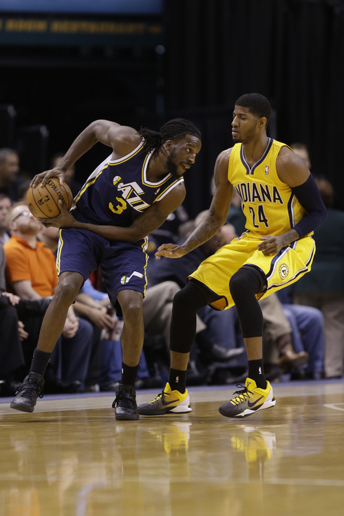 Indiana Pacers small forward Paul George, right, guards Utah Jazz small forward DeMarre Carroll in the first half of an NBA basketball game in Indianapolis, Wednesday, Dec. 19, 2012.  (AP Photo/Michael Conroy)