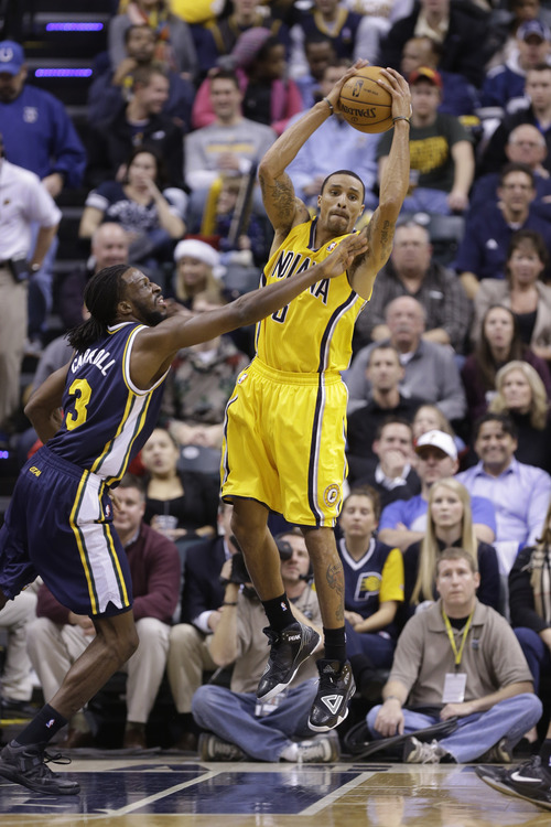 Indiana Pacers point guard George Hill makes a pass over Utah Jazz small forward DeMarre Carroll in the first half of an NBA basketball game in Indianapolis, Wednesday, Dec. 19, 2012.  (AP Photo/Michael Conroy)