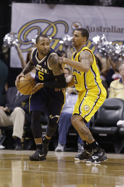 Utah Jazz point guard Mo Williams, left, is guarded by Indiana Pacers point guard George Hill in the first half of an NBA basketball game in Indianapolis, Wednesday, Dec. 19, 2012.  (AP Photo/Michael Conroy)