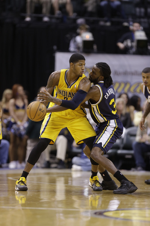 Utah Jazz small forward DeMarre Carroll, right, tries to knock the ball away from Indiana Pacers small forward Paul George in the second half of an NBA basketball game in Indianapolis, Wednesday, Dec. 19, 2012. The Pacers beat the Jazz 104-84.  (AP Photo/Michael Conroy)