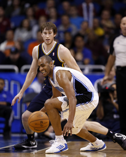 Orlando Magic guard Arron Afflalo (4) tries to recover the loose ball against Utah Jazz guard Gordon Hayward (20) during the second half of an NBA basketball game, Sunday, Dec. 23, 2012, in Orlando, Fla. (AP Photo/Scott Iskowitz)