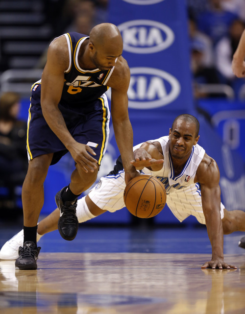 Utah Jazz guard Jamaal Tinsley (6) grabs the loose ball away from a diving Orlando Magic guard Arron Afflalo (4) during the second half of an NBA basketball game, Sunday, Dec. 23, 2012, in Orlando, Fla. (AP Photo/Scott Iskowitz)