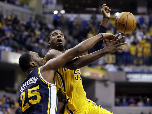Utah Jazz center Al Jefferson (25) fouls Indiana Pacers center Roy Hibbert in the first half of an NBA basketball game in Indianapolis, Wednesday, Dec. 19, 2012. (AP Photo/Michael Conroy)