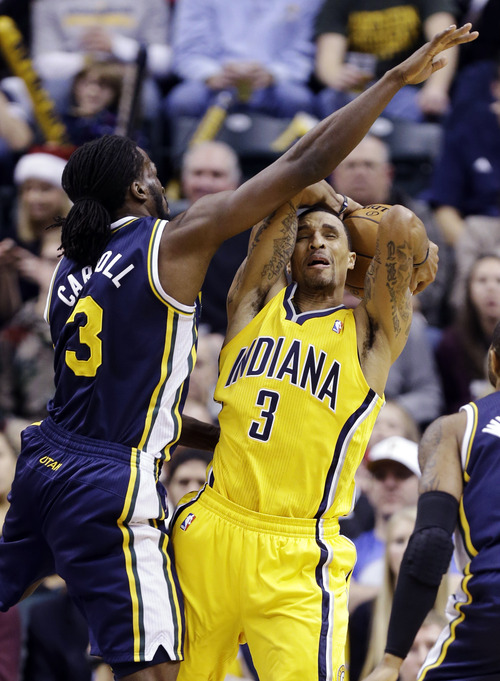 Indiana Pacers guard George Hill (3) is fouled by Utah Jazz forward DeMarre Carroll as he grabs a rebound in the first half of an NBA basketball game in Indianapolis, Wednesday, Dec. 19, 2012. (AP Photo/Michael Conroy)