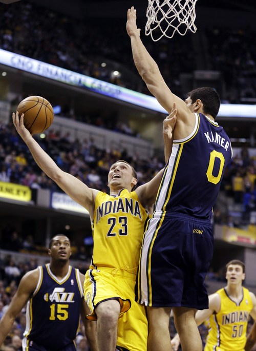 Indiana Pacers guard Ben Hansbrough (23) pushes off Utah Jazz center Enes Kanter (0) as he shoots in the first half of an NBA basketball game in Indianapolis, Wednesday, Dec. 19, 2012. (AP Photo/Michael Conroy)