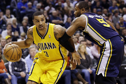 Indiana Pacers guard George Hill (3) drives on Utah Jazz guard Mo Williams in the first half of an NBA basketball game in Indianapolis, Wednesday, Dec. 19, 2012. (AP Photo/Michael Conroy)