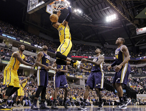 Indiana Pacers forward Paul George dunks over Utah Jazz's Al Jefferson (25), DeMarre Carroll (3), Marvin Williams and Paul Millsap (24) and Pacers' with teammate Roy Hibbert (55) in the first half of an NBA basketball game in Indianapolis, Wednesday, Dec. 19, 2012. (AP Photo/Michael Conroy)