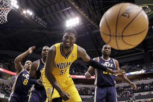 Indiana Pacers center Roy Hibbert (55) loses the ball out of bounds in front of Utah Jazz's Randy Foye (8), Paul Millsap and Al Jefferson (25) in the first half of an NBA basketball game in Indianapolis, Wednesday, Dec. 19, 2012. (AP Photo/Michael Conroy)