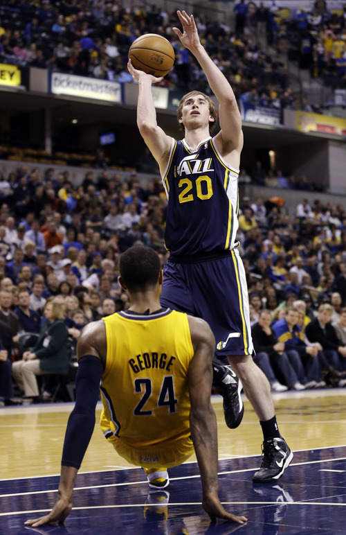 Indiana Pacers forward Paul George, bottom, draws the charge from Utah Jazz guard Gordon Hayward (20) in the second half of an NBA basketball game in Indianapolis, Wednesday, Dec. 19, 2012. The Pacers won 104-84. (AP Photo/Michael Conroy)