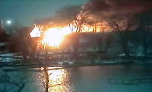 This image taken from video provided by WHAM13-TV, shows a wide view of homes on fire in an area where a gunman ambushed four volunteer firefighters responding to an intense pre-dawn house fire early Monday, Dec. 24, 2012, in Webster, N.Y., killing two before ending up dead himself, authorities said. Police used an armored vehicle to evacuate more than 30 nearby residents. (AP Photo/WHAM13-TV via AP video)