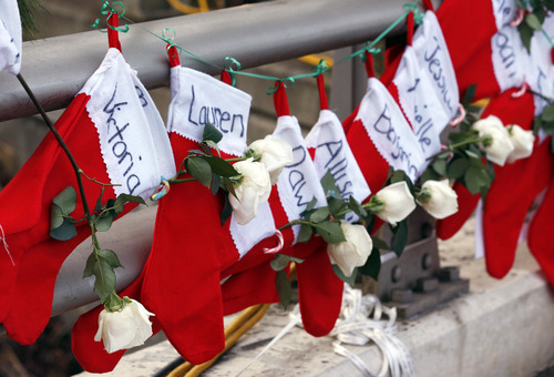 FILE - In this Wednesday, Dec. 19, 2012 file photo, Christmas stockings with the names of shooting victims hang from railing near a makeshift memorial near the town Christmas tree in the Sandy Hook village of Newtown, Conn. (AP Photo/Julio Cortez, File)