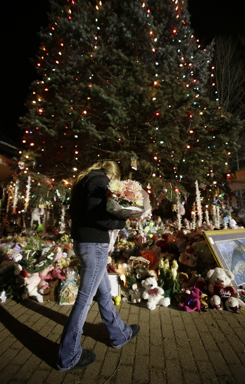 FILE - In this Thursday, Dec. 20, 2012 file photo, a woman with flowers walks past a Christmas tree which has become a memorial to the Newtown shooting victims in Newtown, Conn. In the wake of the shooting, the grieving town is trying to find meaning in Christmas. (AP Photo/Seth Wenig, File)