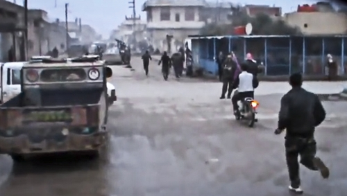 This Sunday, Dec. 23, 2012 image taken from video obtained from the Shaam News Network, which has been authenticated based on its contents and other AP reporting, shows Free Syrian Army fighters running towards the scene after a government airstrike hit Hama Suburb of Halfaya, Syria. A government airstrike Sunday on a bakery in a rebel-held town in central Syria killed tens of people, which left scattered bodies and debris up and down a street, and more than a dozen wounded were trapped in tangled heap of dirt and rubble, activists said. (AP Photo/Shaam News Network via AP video)