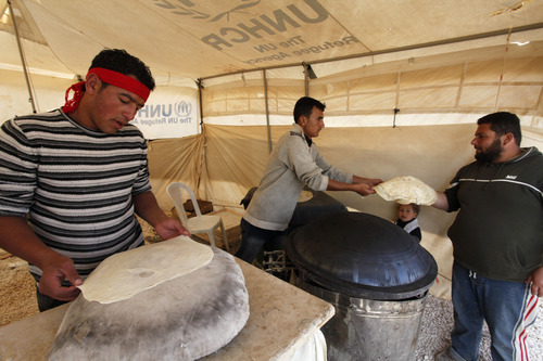 Syrian refugees bake bread at their tent bakery in Zaatari Syrian refugee camp, near the Syrian border in Mafraq, Jordan, Tuesday, Dec. 25, 2012. (AP Photo/Mohammad Hannon)